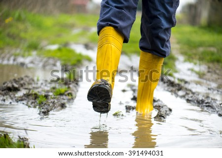 Human leg with Yellow Muddy rubber boots on wet silt - stock photo