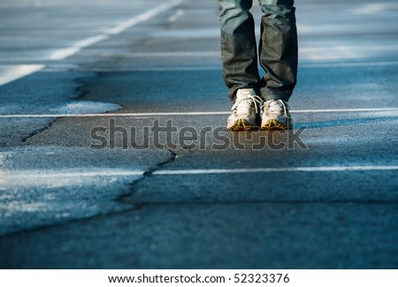 Human legs in sneakers standing on square