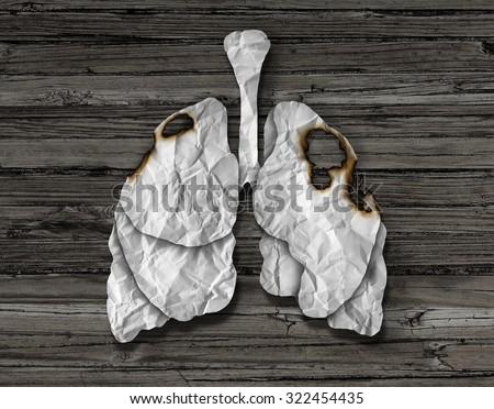 Human lung cancer concept or illness symbol as a decline in respiratory function caused by a tumor disease as the organ made of crumpled white paper with burnt holes on a wood background. - stock photo