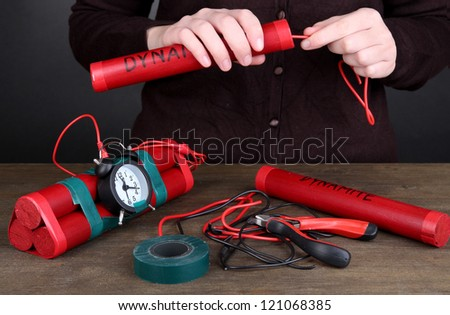 Human makes timebomb on wooden table on black background - stock photo