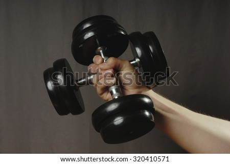 Human male caucasian hand holding two black iron dumbbells during exercise. Gray background.  - stock photo