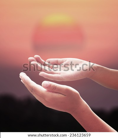 Human open empty hands with palms up over blurred big sun on sunset background. Merry Christmas Card, Thankful, Repentance, Adoration, Glorify, Peace, Evangelical, Hallelujah concept