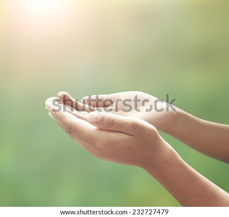 Human open empty hands with palms up, over blurred nature background.