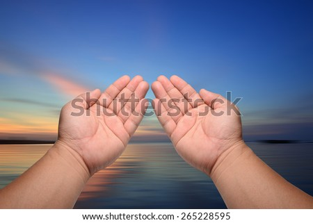 Human open empty hands with palms up, over blurred nature background