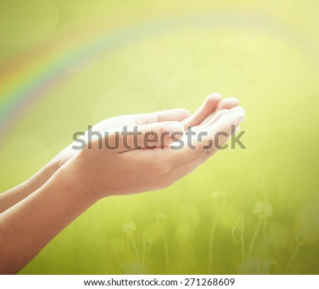 Human open empty hands with palms up over blurred sunset background.