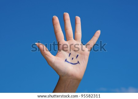 Human palm with smile on blue sky background - stock photo