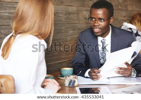 Human resource concept. Portrait of African American HR director wearing formal suit interviewing redhead Caucasian female, checking her resume during a meeting at a coffee shop. Business and career - stock photo