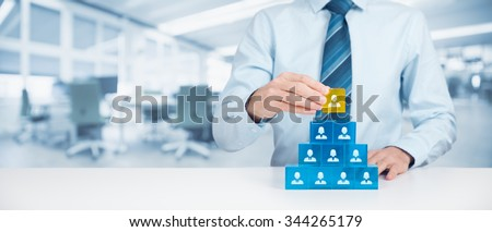 Human resources and corporate hierarchy concept - recruiter complete team by one leader person (CEO) represented by gold cube and icon. Wide banner composition with office in background.