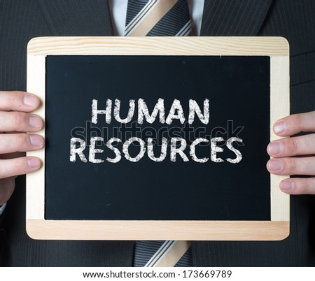 Human resources. Business man holding board on the background with business word  - stock photo