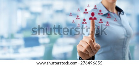 Human resources, CRM and social networking concept - female officer choose person (employee) represented by icon. Out of focused office in background, wide composition.  - stock photo