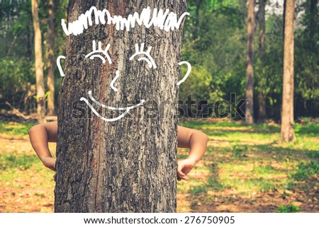 Human's arm akimbo on tree trunk with drawing smile face of tree, protect the forest and save the environment lifestyle concept - stock photo