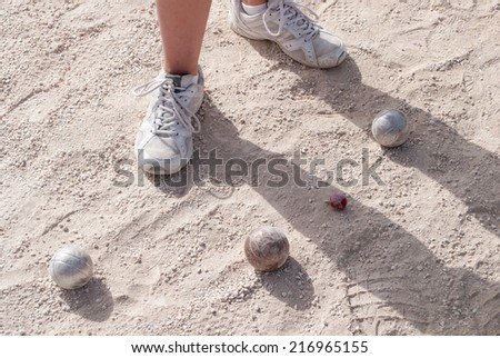 Human's foots in front of petanque balls and a small red jack - stock photo