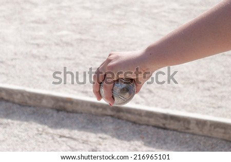 Human's hand holding a petanque ball before throwing it - stock photo