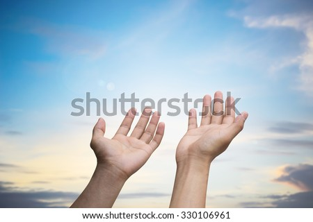 Human's hands pray on blurred beautiful sunrise nature background:man hands praying,forgiveness,helping from heaven:soft focused concept.religious and ceremony conceptual. - stock photo