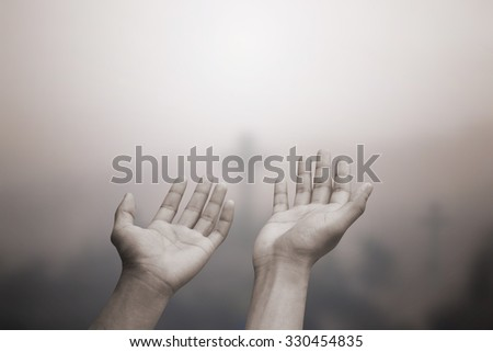 human's hands praying cross (symbols of Christ religious) on blurred churchyard background:hand of soul open receiving power from god.religion concept.human prayer concept.image in sepia tone colored. - stock photo
