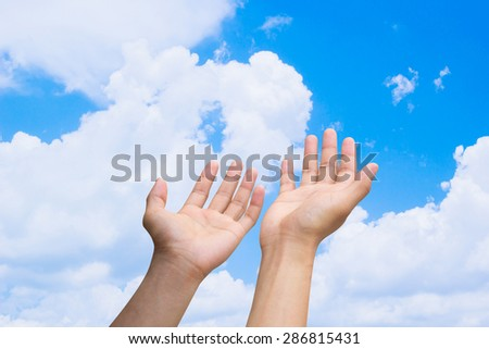 human's hands praying on blurred blue sky background , soft focused. - stock photo