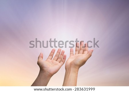 human's hands praying on blurred twilight sky background , soft focused. - stock photo
