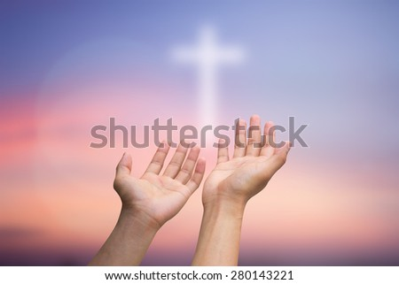 human's hands praying with cross blurred twilight sky background , soft focused. - stock photo