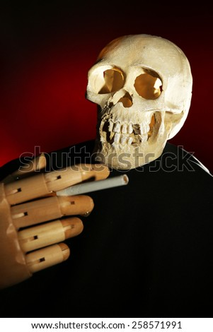 Human scull and wooden hand with cigarette on dark color background - stock photo