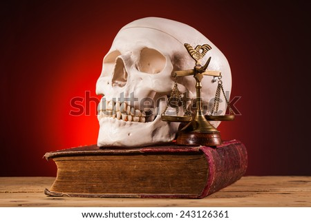 human scull  scales of justice and old book - stock photo