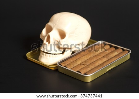 Human scull with Metal Cigar Box on black bacground - stock photo