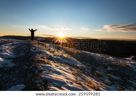Human silhouette greeting the sunrise in a snowy field in the mountain - stock photo