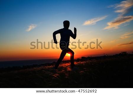 Human silhouette running against sunset sky - stock photo