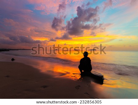 Human Silhouette sitting on the rock with sunset background