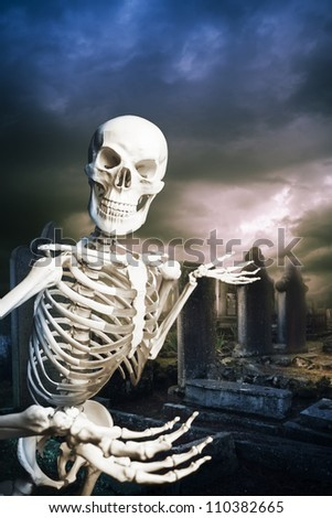 human skeleton in a graveyard on Halloween - stock photo
