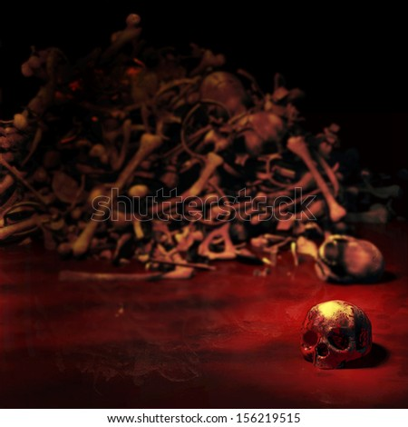 Human Skull - a bloody human skull lying in a pool of blood in front of a pile of bones.  Focus on the skull. Happy Halloween. - stock photo