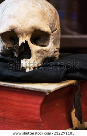 Human skull and old book. Scary theme. - stock photo