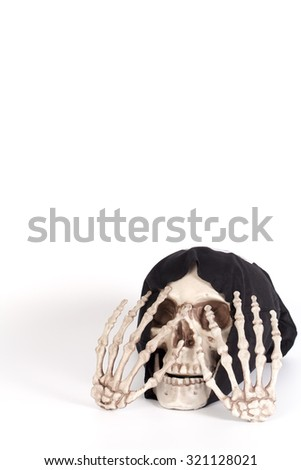 Human Skull Close your eyes with Human Hand and devil black cap - stock photo