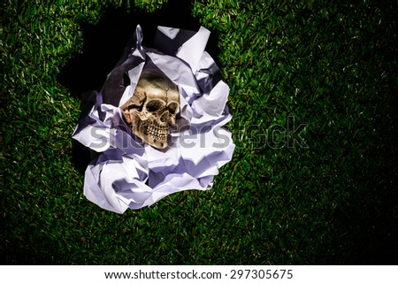 Human skull in Crumpled paper on Green grass background - stock photo