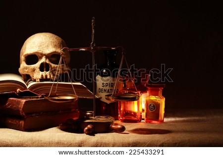 Human skull on old books near weight scales and ancient glass flasks - stock photo