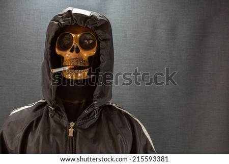 Human skull smoking a cigarette on a black background, Cigarette very dangerous for people. Please don't smoke.Halloween day.