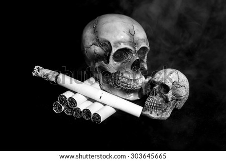 Human skull smoking the cigarette with some smoke in black and white tone. - stock photo