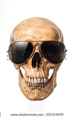 Human skull wearing old sunglasses on white background - stock photo