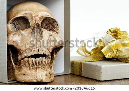 Human Skull with a gift box - stock photo