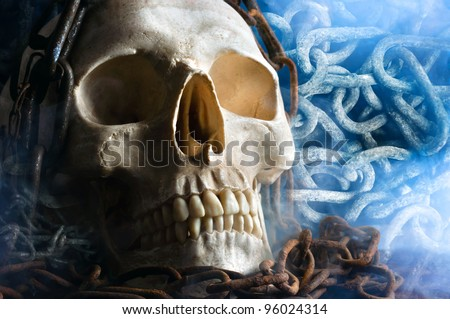 human skull with chain and smoke - stock photo