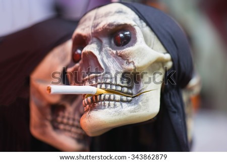 Human skull with cigarette on mouth. Concept of smoking damage