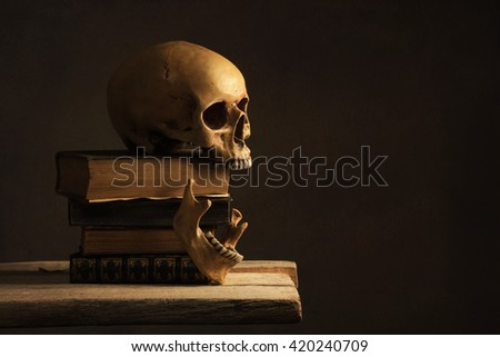 human Skull with Jawbone on old Books - stock photo