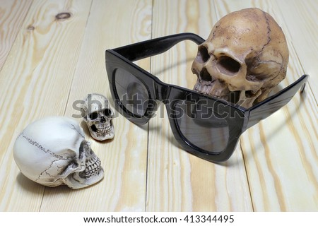 Human skull with  old sunglasses on wood background, still life style. - stock photo