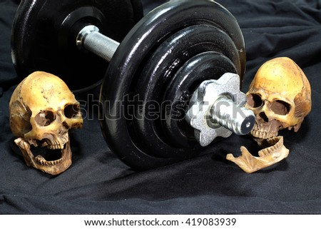 human skulls and Heavy black dumbbells on black background. concept still life style and workout