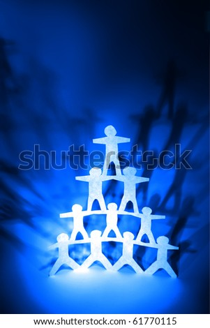 Human team pyramid on blue color background - stock photo