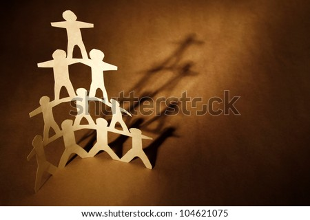 Human team pyramid on brown background - stock photo