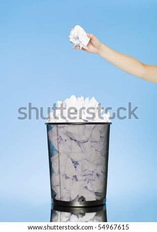 Human trowing a paper to a wastebasket on blue background - stock photo
