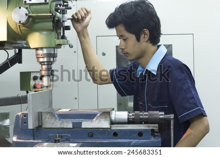 Human using Milling machine face on top stainless steel on bench vise - stock photo