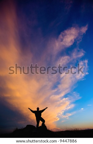 Human with outreached arms silhouetted against a beautiful evening sunset - stock photo