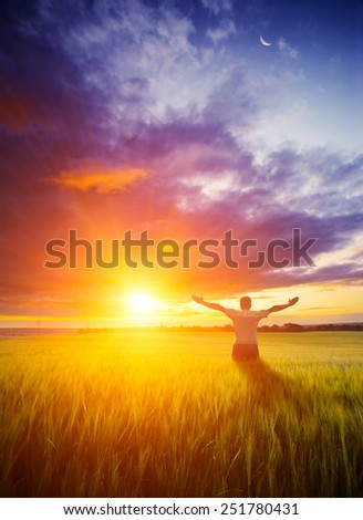 Human with raised hands stay in a wheat field welcome bright colorful sunset