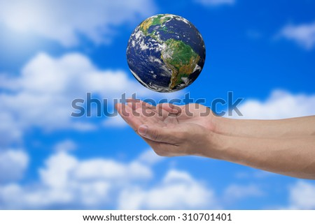 humans hand open palms gesture for show world over blurred blue sky backgrounds : human hand safe world life concept,ecology concept.Elements of this image furnished by NASA. - stock photo